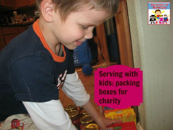 serving others with kids packing boxes for charity